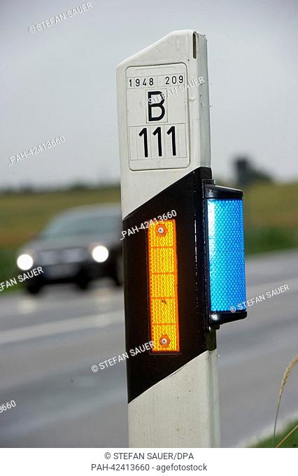 A warning reflector for wild animals glows on a marker post on highway B111 near Wolgast, Germany, 02 September 2013. The reflector's blue colour signalizes...
