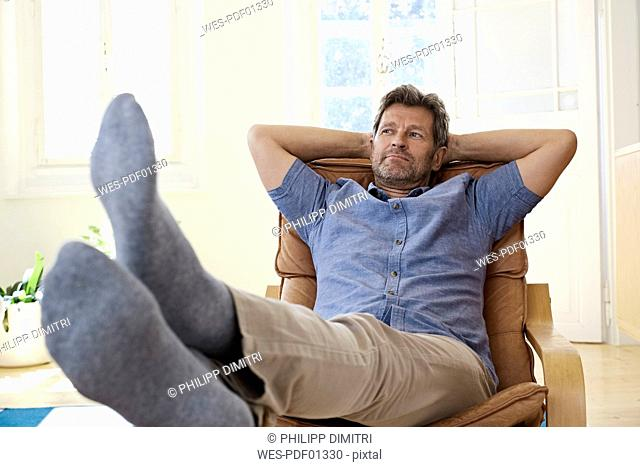Man sitting in arm chair with feet up, daydreaming