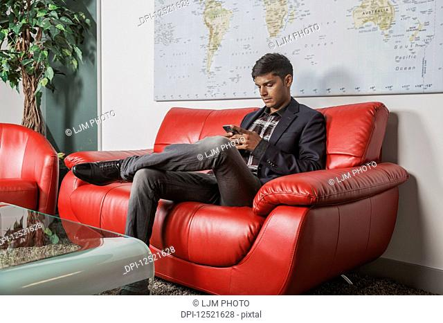 Young millennial businessman using his smart phone in the lobby of a workplace; Sherwood Park, Alberta, Canada