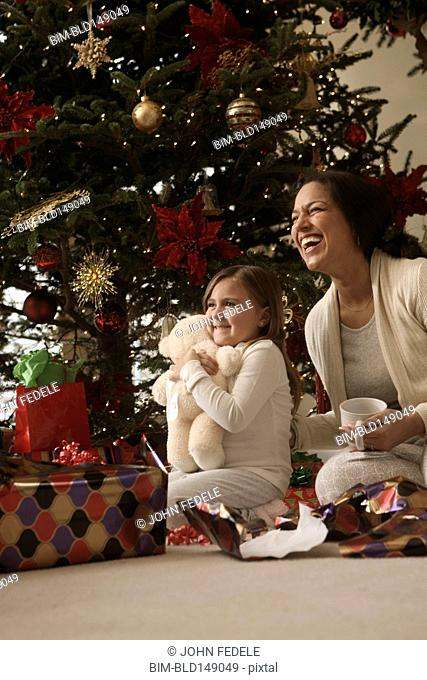 Mixed race mother and daughter opening gifts Christmas morning