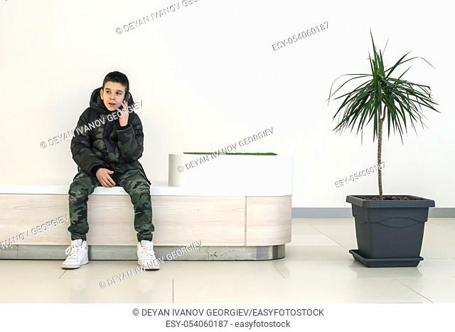 Teenager talking on smartphone in modern commercial center. Bench and flower in a pot. Modern building interior. Technology and communication concept with child...