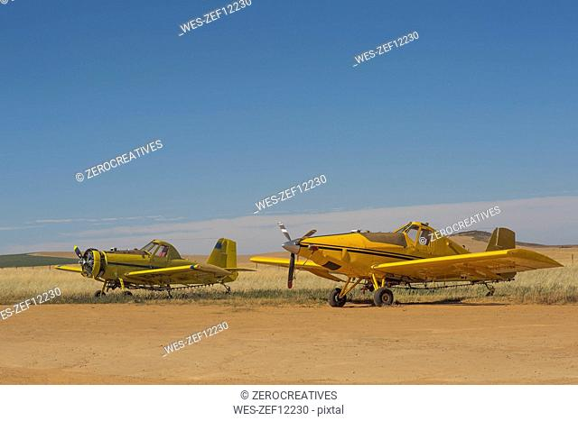 Two crop dusting planes by field