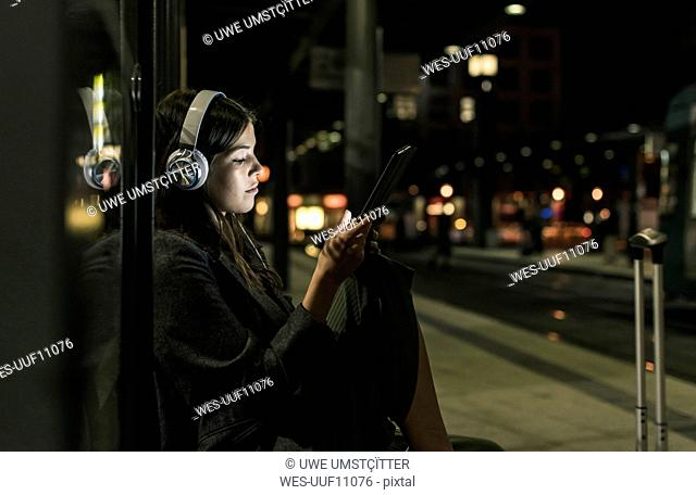 Young woman with headphones waiting at the station by night using tablet