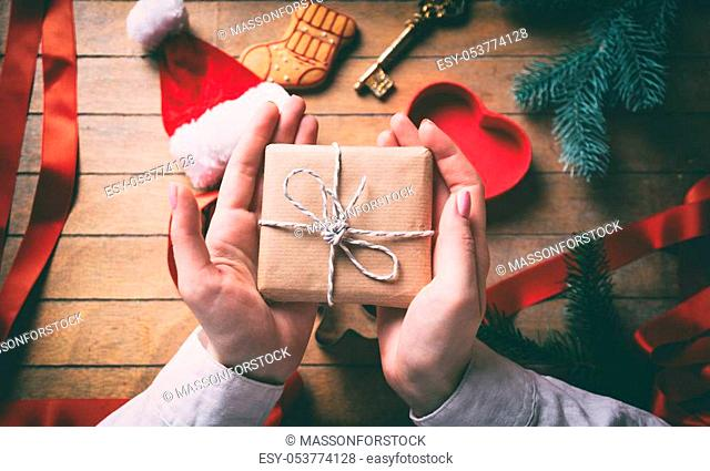 Young woman hands wrapping christmas gifts and cookies on wooden background, Photo in old color image style