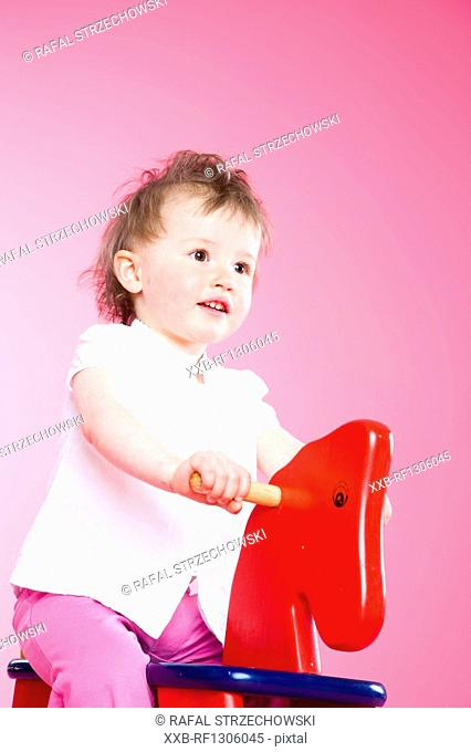 toddler girl riding on rocking horse