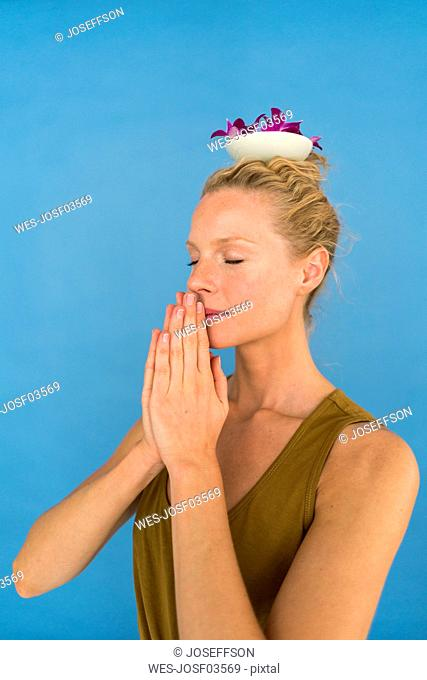 Blond woman with bowl and orchid petals on her head, blue background