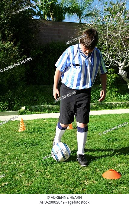 Youth in striped football shirt dribbles ball around orange cones