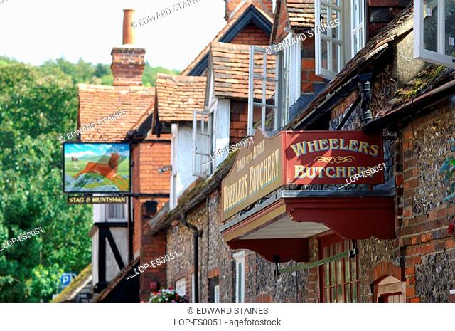 England, Buckinghamshire, Hambleden, Pub and butcher signs with houses at Hambleden Village. The name is Anglo Saxon in origin and means 'crooked or undulating...