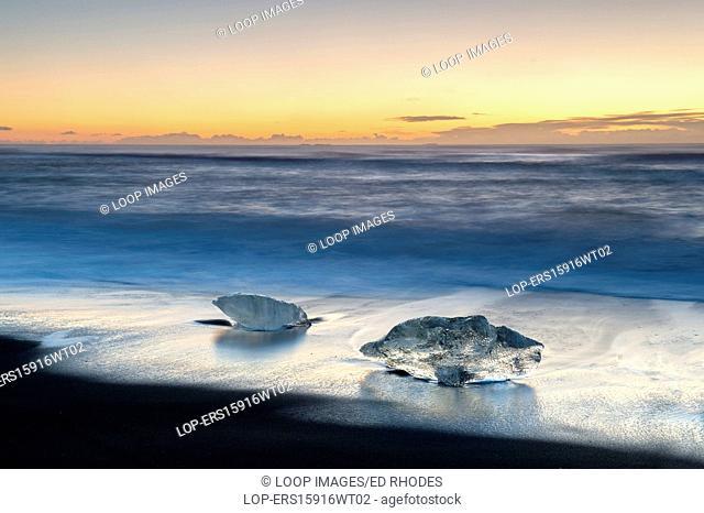Icebergs washed up on Jokulsa volcanic beach at sunrise