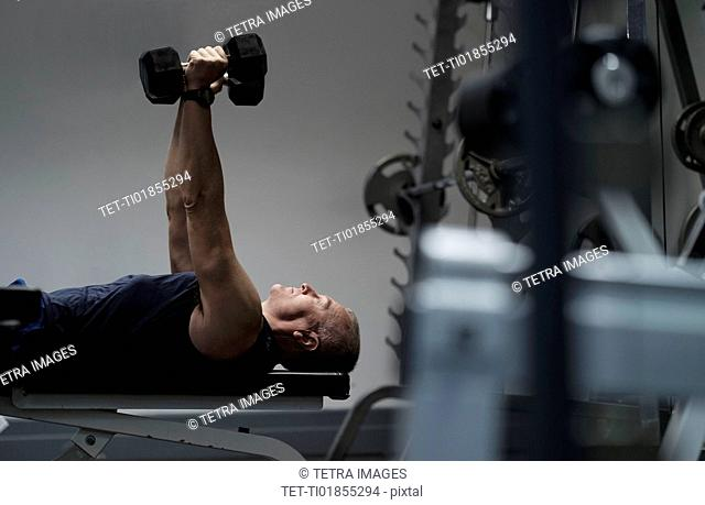 Man exercising with dumbbells on weight bench