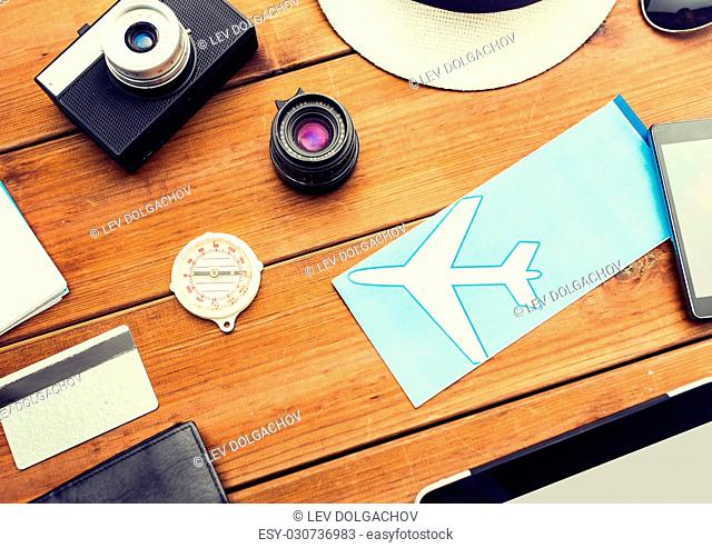 vacation, travel, tourism and objects concept - close up of camera and traveler personal stuff