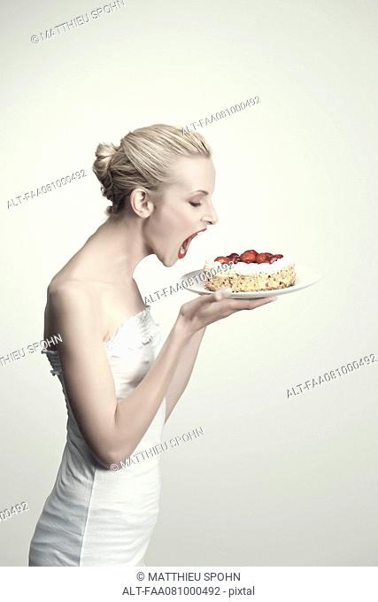Young woman holding strawberry cake with open mouth, side view, portrait