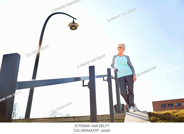 Low angle view of woman leaning against banister on steps looking away