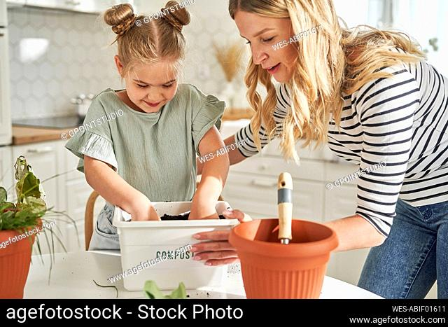Woman teaching girl to make compost in container at home