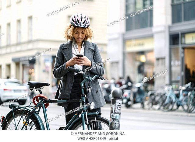 Woman with bicycle and smartphone in the city, Berlin, Germany