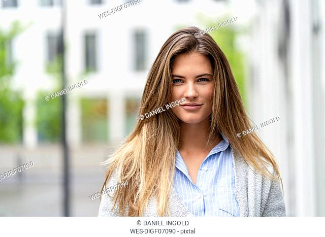 Portrait of young businesswoman, office building in the background