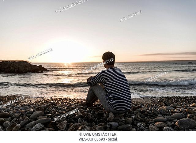 France, Bretagne, Crozon peninsula, woman sitting on stony beach at sunset