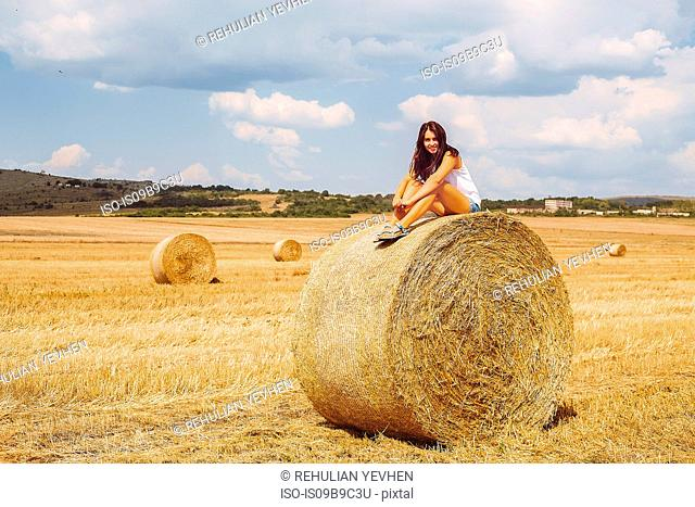 Woman sitting on top of hay bale looking at camera smiling