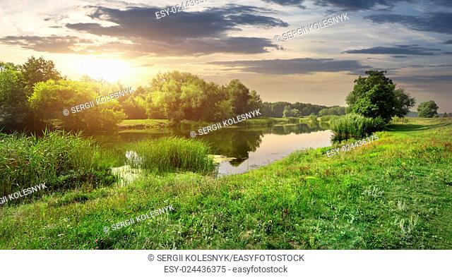 Sunny sunset over calm river in the forest