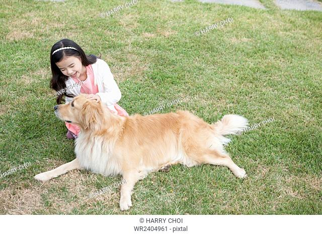 Girl playing with her dog on the grass at the yard in Jeju