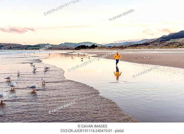 Little boy running at beach with reflection