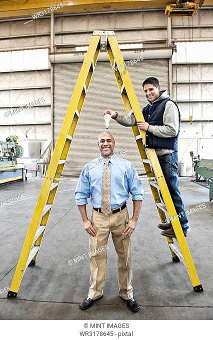 Black man factory owner and young Caucasian man factory worker goofing off together on the floor of a sheet metal factory