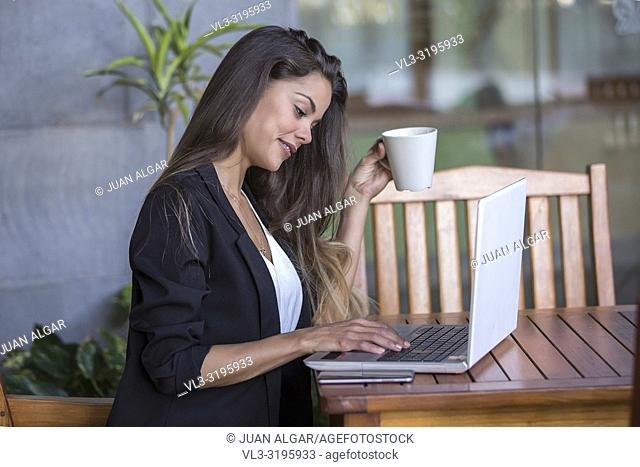 Stylish young brunette holding cup and sitting at table on hotel terrace working on laptop in daylight