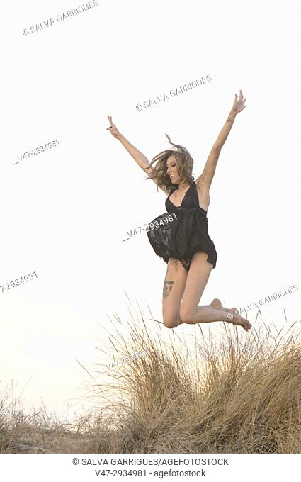 Woman jumping through the air on a beach dune, Valencia, Spain