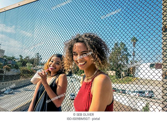 Two young women laughing on highway footbridge, Los Angeles, California, USA