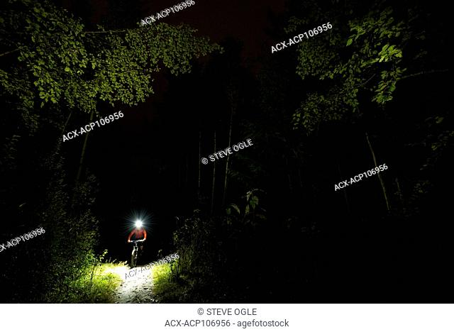 A mountain biker goes on a night ride using a headlamp, Nelson, BC