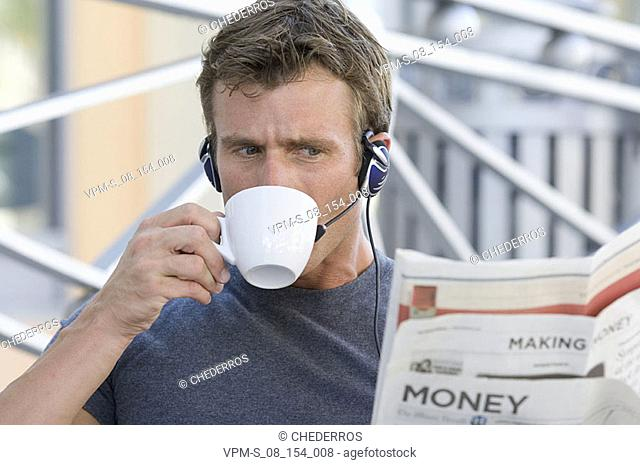 Close-up of a mid adult man wearing a headset and having a cup of tea