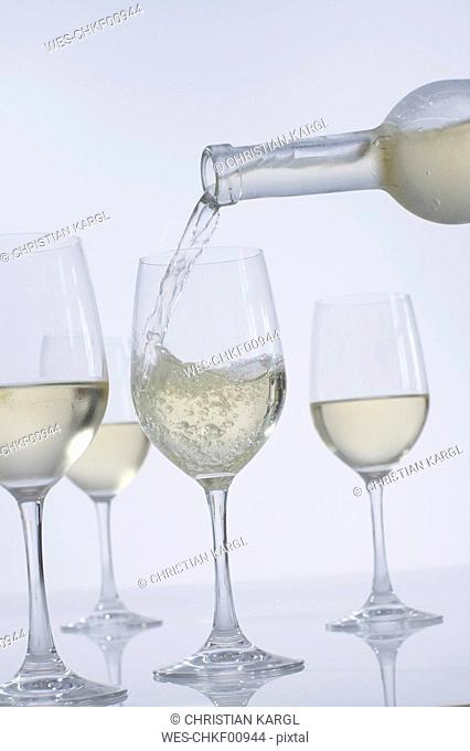 Pouring white wine in wine glasses