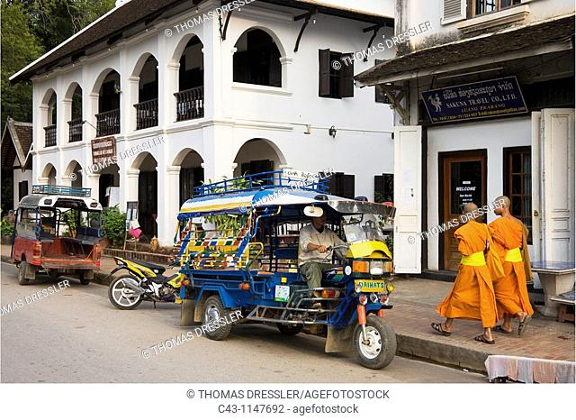 Laos - Buddhist novices next to a Tuk-Tuk motorcycle taxi in the main road of Luang Prabang which in 1995 was declared UNESCO World Heritage Site in recognition...