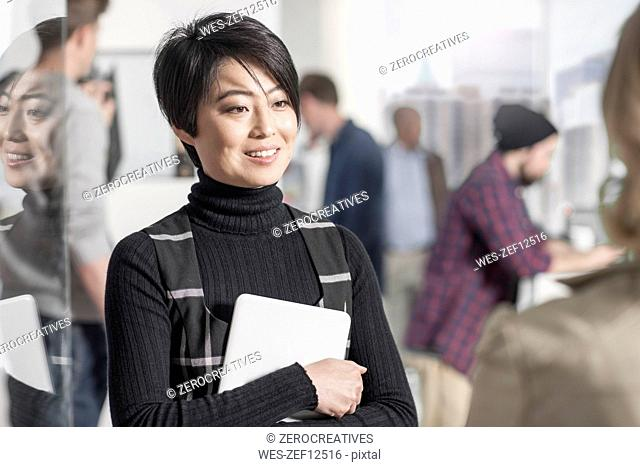 Portrait of smiling woman holding a tablet in office