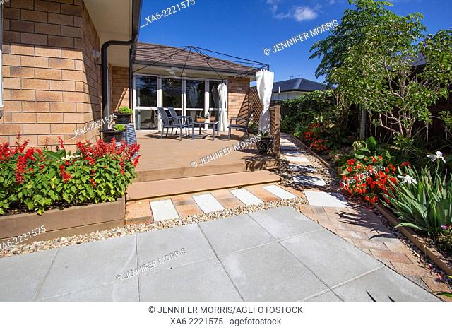 A patio on a deck with pavers and plants around in a back garden. New Zealand, Pukekohe, Auckland