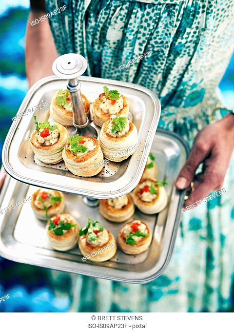 Retro styled woman serving vol au vents from cake stand
