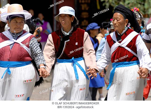 Three women in traditional costume of the Naxi minority holding hands and dancing on the main square in Lijiang, Yunnan, Southwest China, Asia