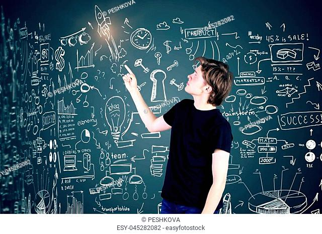 Side view of young businessman pointing at business sketch on dark background. Leadership concept