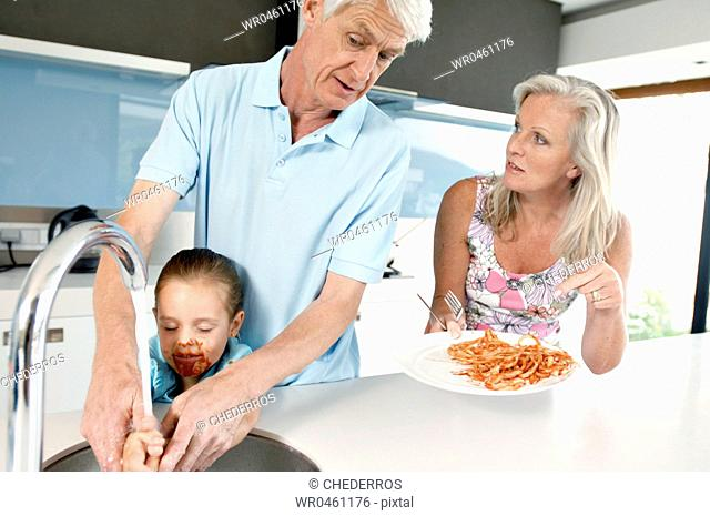 Senior man helping her granddaughter to wash her hands with his wife looking at him