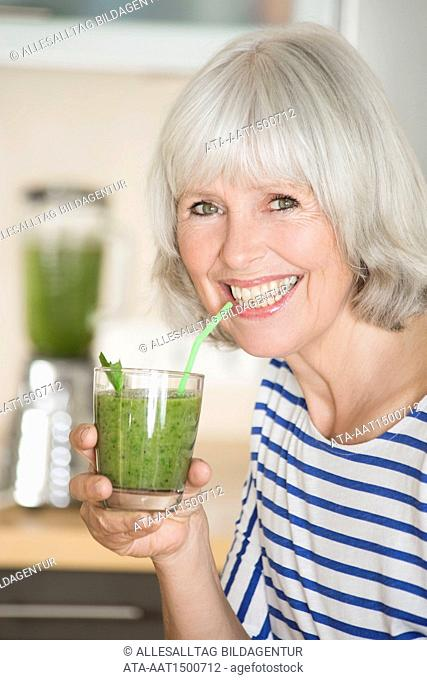 Elderly woman drinking a green smoothie