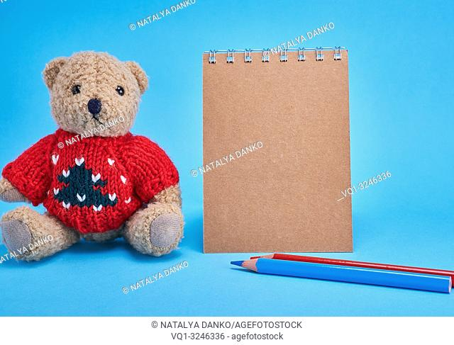 blank brown spiral notepad with brown pages, pencils and a little brown teddy bear on a blue background