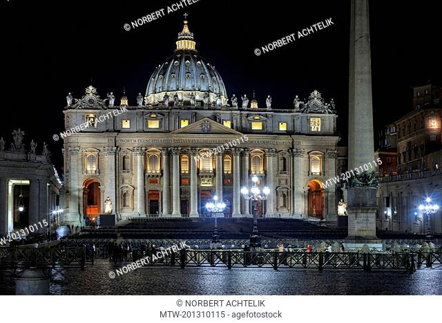 Illuminated cathedral and column at St Peter Square, Rome, Italy