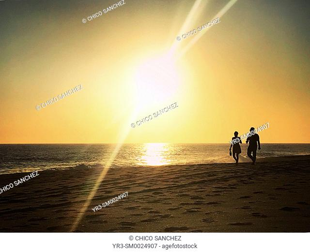 A couple walks at sunset in the Pacific Ocean coast in the beach in Todos Santos, Baja California Sur, Mexico