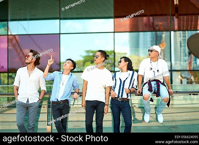 a group of five young asian adults hanging out together on street