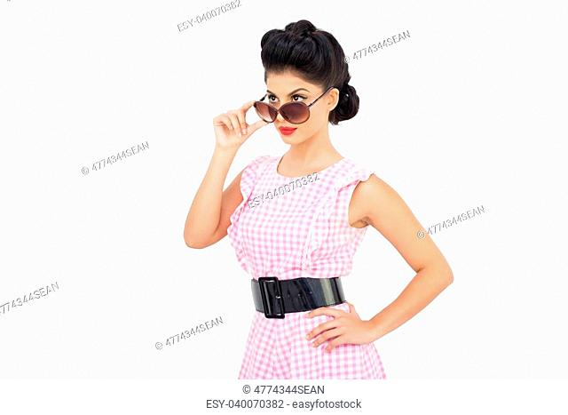 Charming black hair model looking over her sunglasses on white background