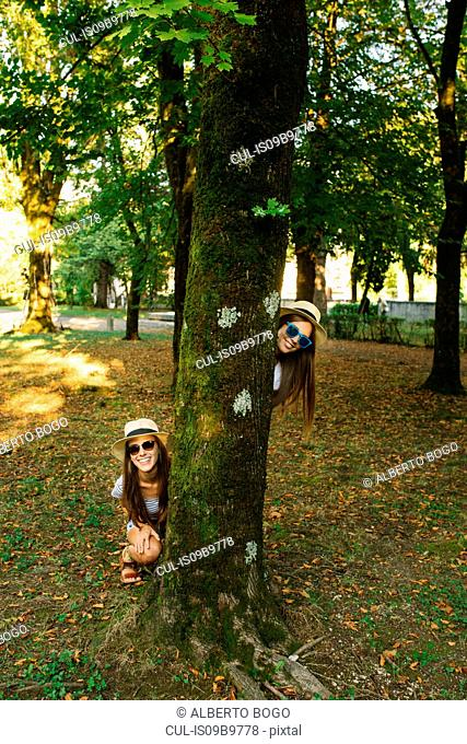 Portrait of two young female friends in trilby hats behind park tree