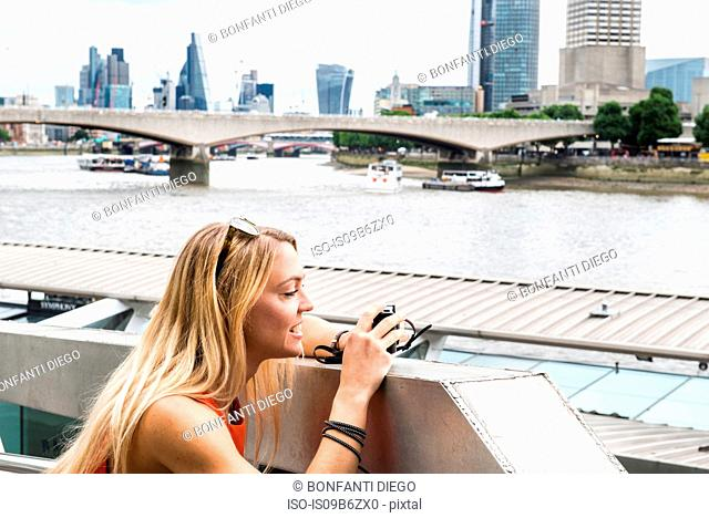 Female tourist leaning on wall, photographing London view