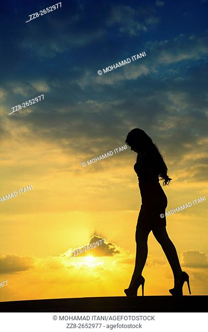 Full length woman's silhouette walking against a dramatic sunset