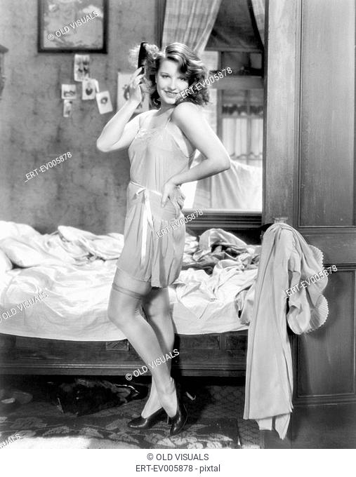 Woman in a slip and combing her hair posing sexily in her bedroom All persons depicted are not longer living and no estate exists Supplier warranties that there...