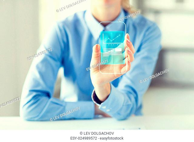business, success, statistics, technology and people concept - close up of woman hand holding and showing transparent smartphone with chart at office